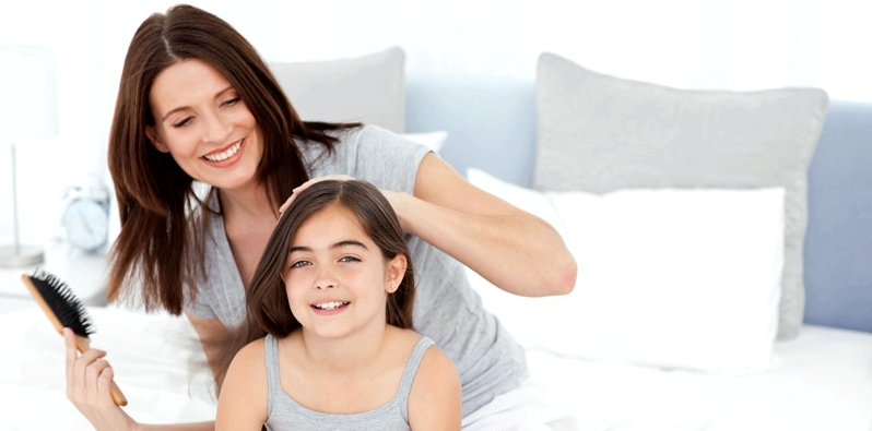 Mutter kämmt Haare der Tochter