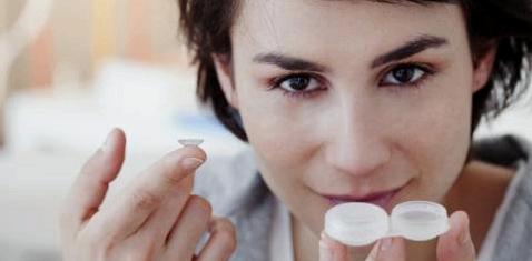 Eine Frau hält eine Kontaktlinse in der Hand