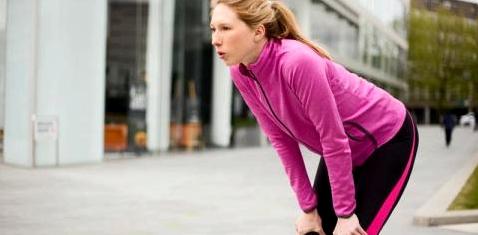 Frau schnappt nach Luft beim Laufen