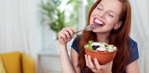 Eine Frau isst genüsslich Salat