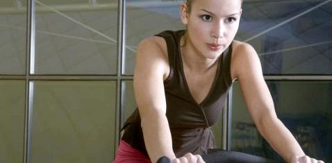 Eine Frau trainiert auf einem Ergometer
