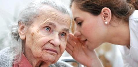 Eine Pflegerin spricht einer alten Frau ins Ohr