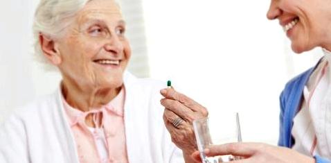 Eine junge Frau gibt einer alten Frau eine Tablette