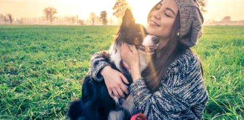 Eine Frau umarmt einen Hund
