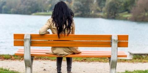 Eine einsame Frau auf der Parkbank