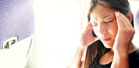 Eine Frau sitzt im Flugzeug und hat Kopfschmerzen