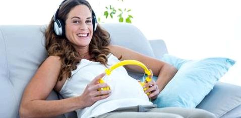Eine Schwangere hält einen Kopfhörer auf ihren Bauch