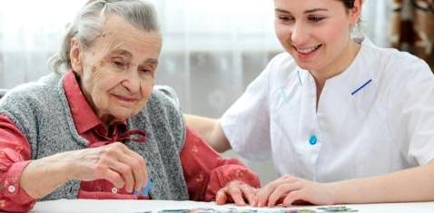 Eine alte Frau puzzelt mit ihrer Pflegerin