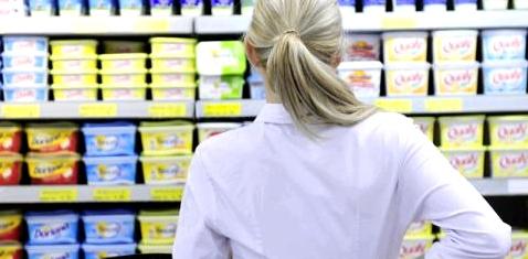 Eine Frau steht vor einem Supermarktregal und denkt nach