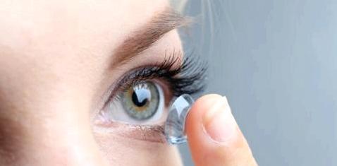 Eine Frau setzt sich eine Kontaktlinse ein