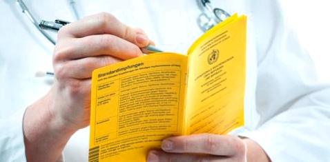 Ein Mediziner hält einen Impfausweis in der Hand
