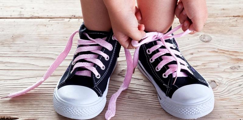 Kind bindet Schuhe zu