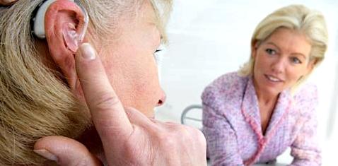 Ältere Frau trägt Hörgerät