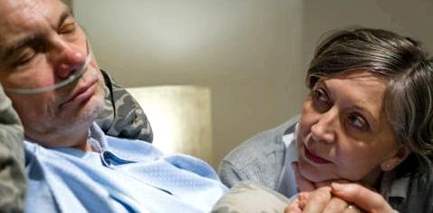 Eine Frau sitzt am Bett eines bewusstlosen Mannes