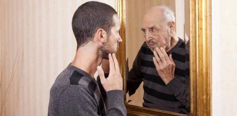 Junger Mann blickt auf sein altes Spiegelbild