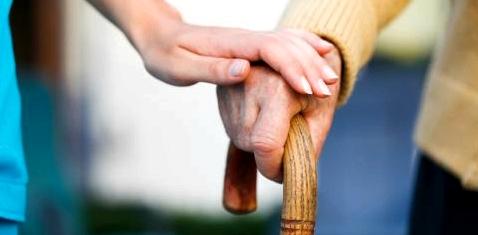 Die Hand einer Pflegerin hält die eines alten Mannes