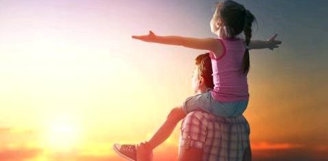 Vater mit Kind auf den Schultern im Sonnenlicht