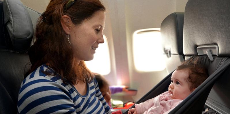Frau mit Baby im Flugzeug