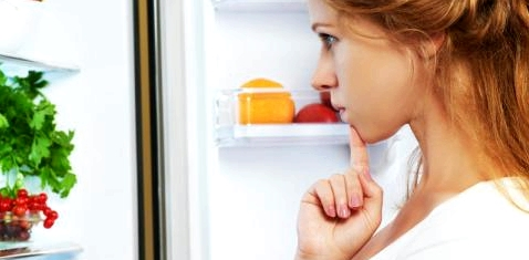 Eine Frau blickt in einen Kühlschrank und denkt nach