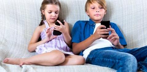 Zwei Kinder sitzen auf einer Couch und spielen mit ihren Handys