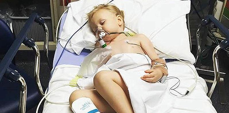 Ein Junge liegt in einem Krankenhausbett