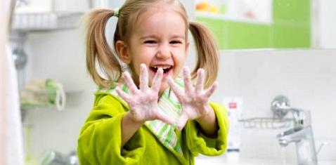 Ein Mädchen hält seine eingeseiften Hände in die Kamera