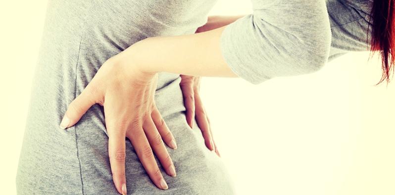 Frau hält sich schmerzende Nieren