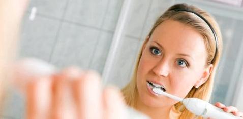 Frau putzt Zähne gegen Zungenbelag