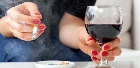 Eine Frau trinkt Wein und raucht
