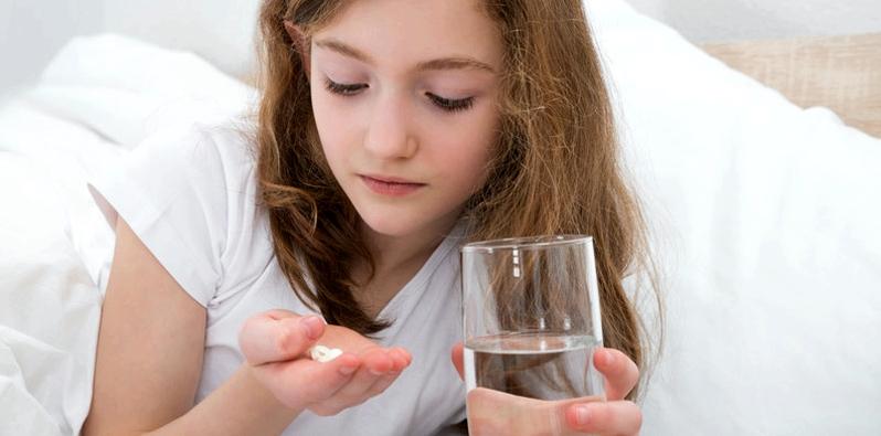 Mädchen nimmt Schmerzmittel ein
