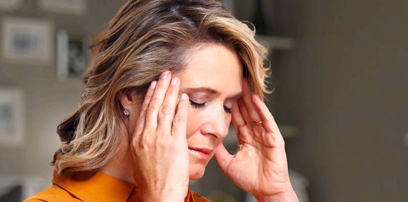 Frau mit Reizdarm hat Kopfschmerzen