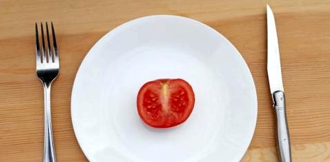 Auf einem Teller liegt eine halbe Tomate