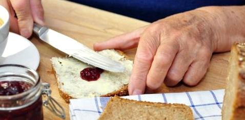 Eine Seniorin schmiert ein Brot