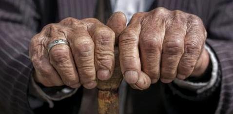 Die Hände eines alten Mannes halten einen Stock