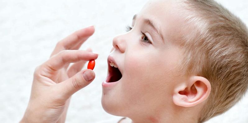 Kind nimmt Tablette ein