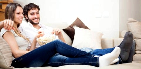 Ein Pärchen sitzt auf einem Sofa und sieht fern