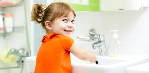 Ein kleines Mädchen wäscht sich die Hände