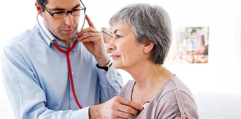 Arzt hört Herz bei Frau ab