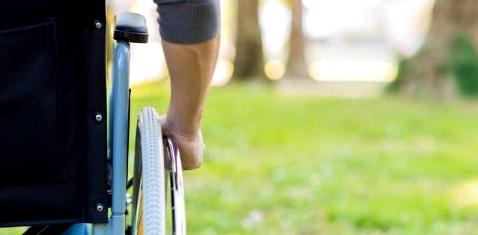 Rückansicht auf einen Mann, der im Rollstuhl sitzt