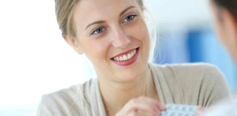 Ein Arzt reicht einer Frau eine Pillenpackung
