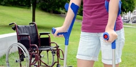 Frau mit Krücken vor Rollstuhl