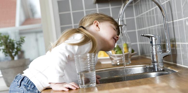 Mädchen trinkt aus Wasserhahn