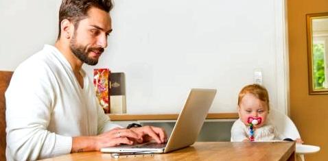 Ein Vater arbeitet zuhause und betreut sein Baby