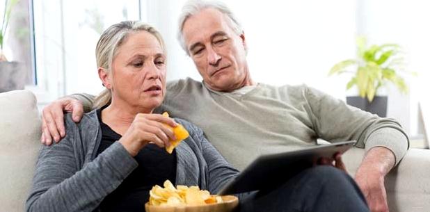 Paar isst Chips auf Couch - Gift für die Leber