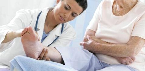 Eine Ärztin untersucht das Bein einer Seniorin