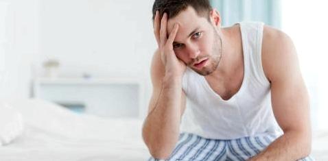 Ein Mann sitzt traurig auf der Bettkante