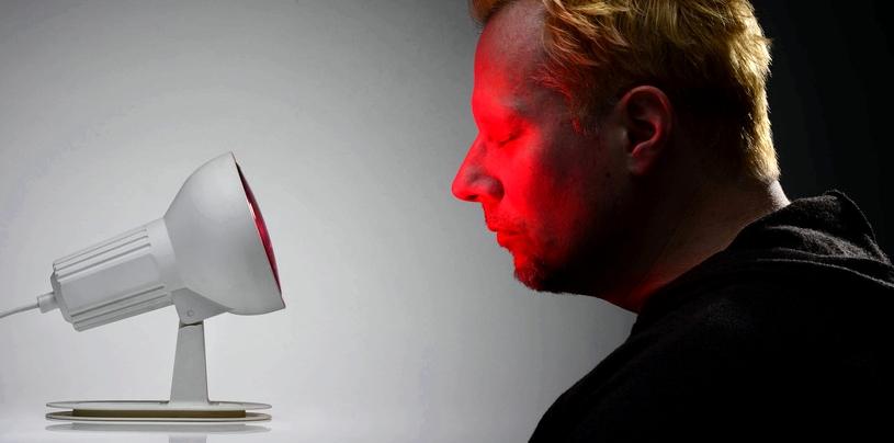 Mann sitzt vor Rotlicht-Lampe