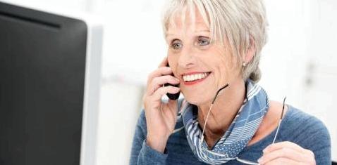 Eine ältere Frau telefoniert vor einem Computer
