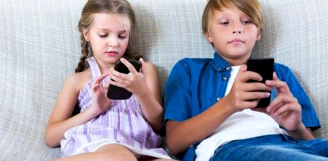 Zwei Kinder sitzen nebeneinander und blicken auf ihre Smartphones