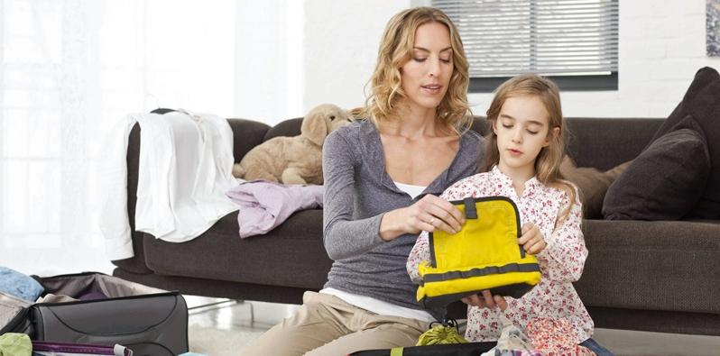 Mutter packt mit Tochter den Koffer